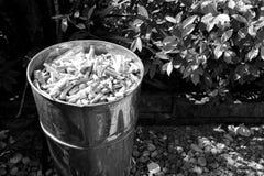 Cigarrillo de las porciones en la arena en compartimiento delante del retrete en fotografía blanco y negro foto de archivo libre de regalías