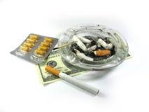 Cigarrillo, dinero, ceniza-basura, y drogas aisladas Fotos de archivo libres de regalías