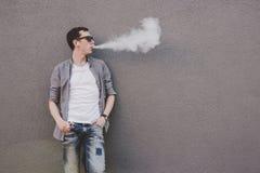 Cigarrillo electrónico que fuma, vaping del hombre joven o vape Fondo gris foto de archivo