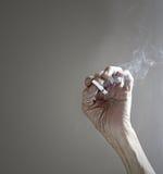 Cigarrillo Emaciated de la explotación agrícola de la mano Imagen de archivo libre de regalías