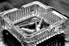 Cigarrillo en el cenicero de cristal Foto de archivo libre de regalías