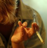 Cigarrillo en una mano femenina Imagen de archivo libre de regalías