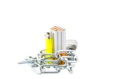 Cigarrillo, encendedor y cadenas I imagen de archivo