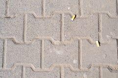 Cigarrillo pero en el pavimento Imagenes de archivo