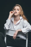 Cigarrillo que fuma de la mujer en silla Fotos de archivo
