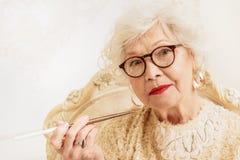 Cigarrillo que fuma de la mujer mayor seria Imagen de archivo