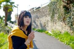 Cigarrillo que fuma de la mujer morena joven afuera Fotos de archivo libres de regalías