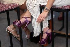 Cigarrillo que fuma en las manos de las mujeres en el fondo de vestidos y pies en zapatos imagenes de archivo