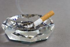 Cigarrillo y cenicero Fotos de archivo