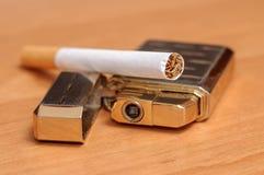 Cigarrillo y encendedores colocados en el piso de madera fotos de archivo libres de regalías