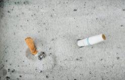 Cigarrillos ahumados en cenicero de la arena Imagen de archivo