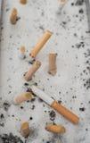 Cigarrillos ahumados en cenicero de la arena Imagen de archivo libre de regalías