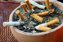Cigarrillos ahumados en un cenicero sucio Fotografía de archivo