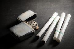 Cigarrillos con el encendedor viejo del metal Foto de archivo libre de regalías