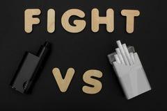 Cigarrillos contra Vape Cigarrillo electrónico sobre un fondo oscuro Dispositivos populares del año - dispositivo vaping moderno Imagenes de archivo