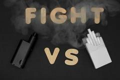 Cigarrillos contra Vape Cigarrillo electrónico sobre un fondo oscuro Dispositivos populares del año - dispositivo vaping moderno Imagen de archivo libre de regalías