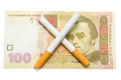 cigarrillos cruzados sobre cientos hrivna Fotografía de archivo