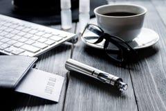 Cigarrillos electrónicos y accesorios para hombre en fondo de madera Foto de archivo