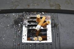 Cigarrillos en cenicero urbano Pare el apego Lifesty no sano Imágenes de archivo libres de regalías