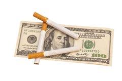 Cigarrillos en cientos billetes de dólar Fotografía de archivo libre de regalías