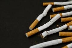 Cigarrillos en fondo negro fotos de archivo libres de regalías