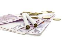 Cigarrillos en moneda europea Fotografía de archivo