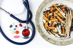Cigarrillos en un cenicero de cristal en un fondo blanco Tratamiento del cáncer de pulmón Estetoscopio y medicación Imágenes de archivo libres de regalías