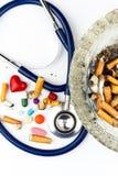 Cigarrillos en un cenicero de cristal en un fondo blanco Tratamiento del cáncer de pulmón Estetoscopio y medicación Foto de archivo
