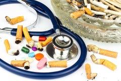 Cigarrillos en un cenicero de cristal en un fondo blanco Tratamiento del cáncer de pulmón Estetoscopio y medicación Fotografía de archivo libre de regalías