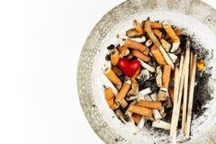 Cigarrillos en un cenicero de cristal en un fondo blanco Tratamiento del cáncer de pulmón Industria de tabaco Fotografía de archivo libre de regalías