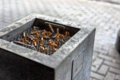 Cigarrillos en un cenicero público Imágenes de archivo libres de regalías