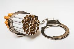 Cigarrillos y esposas - concepto del apego que fuma Fotografía de archivo