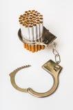 Cigarrillos y esposas - concepto del apego que fuma Foto de archivo libre de regalías