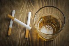 Cigarrillos y vidrio de alcohol que forman la palabra NINGUNA imagenes de archivo