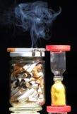 Cigarrillos y vidrio de la hora Imágenes de archivo libres de regalías