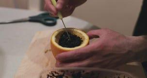 Cigarro da configuração das mãos para o cachimbo de água na laranja filme