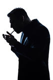 Cigarro de fumo da iluminação do retrato do homem da silhueta Fotografia de Stock Royalty Free