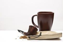 Cigarro de tubulação e um fundo de vidro Imagem de Stock Royalty Free