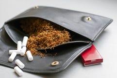 Cigarro do rolamento em um malote de couro com a caixa de papel e os filtros do rollin Fotografia de Stock Royalty Free
