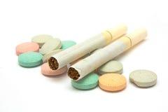 Cigarro dois em poucos comprimidos Fotografia de Stock Royalty Free