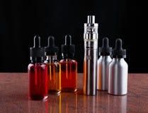 Cigarro e garrafas eletrônicos com líquido do vape no fundo de superfície e preto do granito Foto de Stock Royalty Free