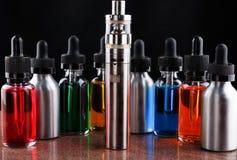 Cigarro e garrafas eletrônicos com líquido do vape no fundo de superfície e preto do granito Fotos de Stock