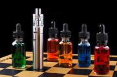 Cigarro e garrafas eletrônicos com líquido do vape no tabuleiro de xadrez e no fundo preto Fotografia de Stock