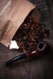Cigarro e tubulação na superfície de madeira Foto de Stock