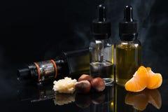 Cigarro eletrônico com sabores diferentes em umas garrafas com reflexão em um fundo preto foto de stock royalty free