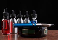 Cigarro eletrônico no cinzeiro e nas garrafas com líquido do vape no fundo preto Imagem de Stock