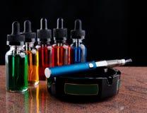 Cigarro eletrônico no cinzeiro e nas garrafas com líquido do vape no fundo preto Imagem de Stock Royalty Free