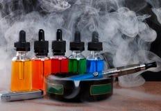 Cigarro eletrônico no cinzeiro, no isqueiro do cigarro e nas garrafas com líquido do vape dentro do vapor no fundo preto Fotografia de Stock Royalty Free