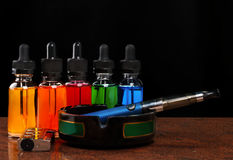 Cigarro eletrônico no cinzeiro, no isqueiro do cigarro e nas garrafas com líquido do vape no fundo preto Fotografia de Stock Royalty Free