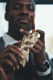 Cigarro que fuma del hombre de negocios afroamericano y billete de banco ardiente del dólar imagenes de archivo